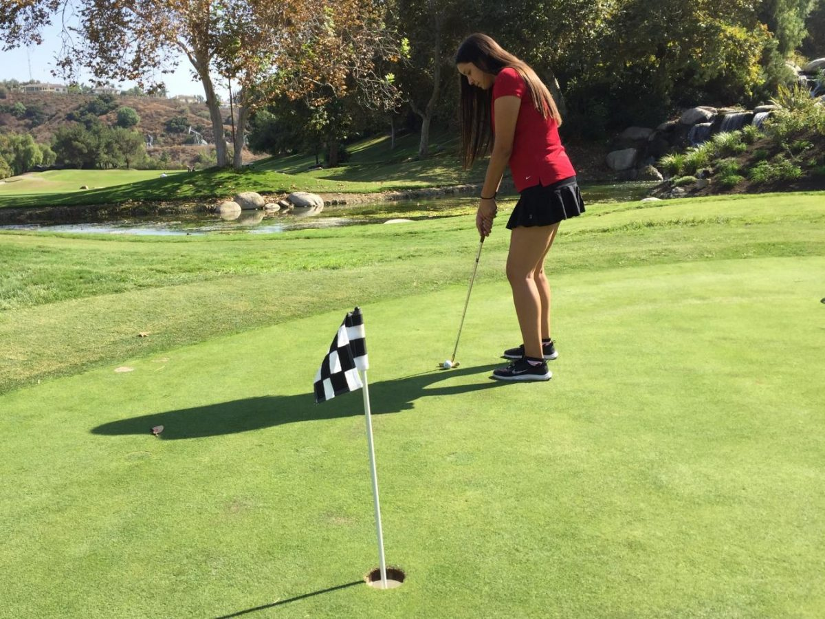Senior Kate Torres practices her putt before a match. Photo by Megan Kim.