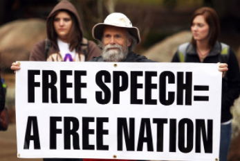 "A man holds a sign saying ""Free speech = a free nation"" at a free speech rally. Source: Wikimedia Commons"