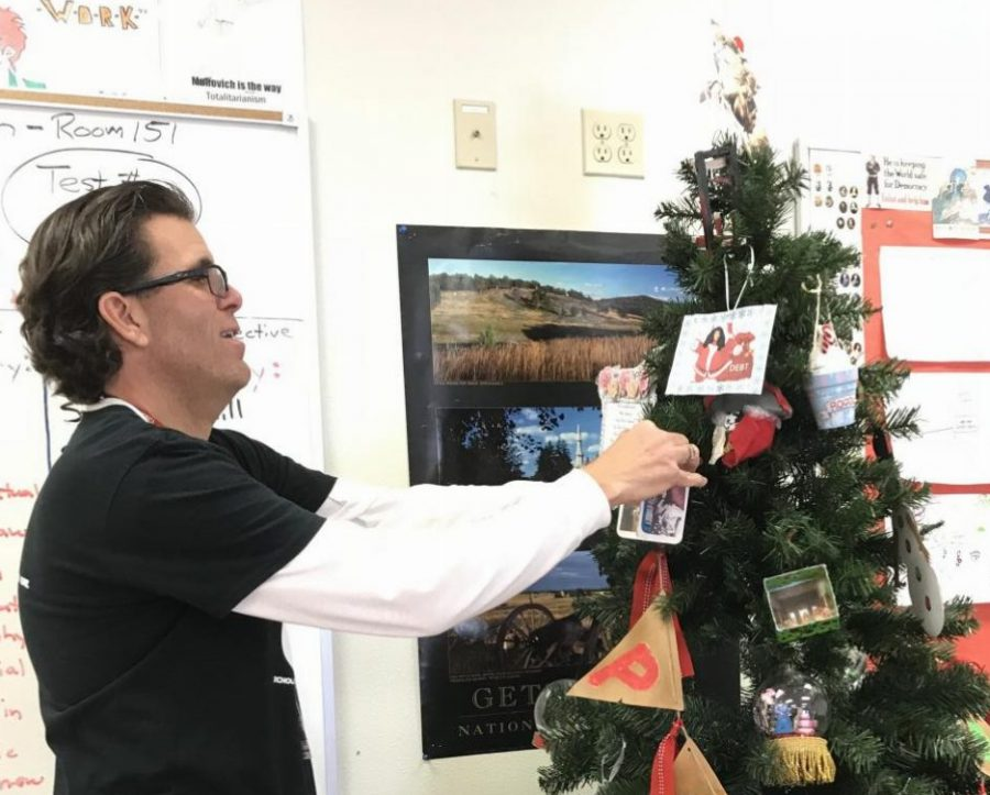 Mike Muhovich puts a student's ornament on the Christmas Tree. Photo by Jamie Ma.