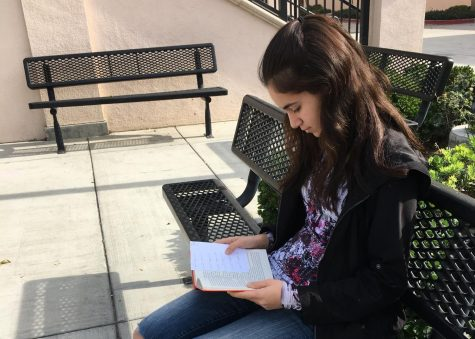Sophomore Claudia Fiallo reads to fulfill her New Year's resolution. Photo by Emma Kelly.