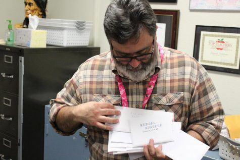 English teacher Leonardo Indelicato flips through letters written by the class of 2018. Photo by Tyler Balsbaugh.