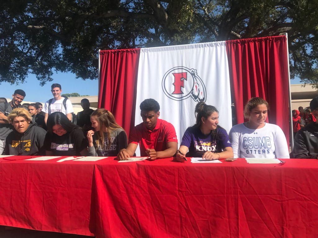 Student athletes sign their commitment letters. Photo courtesy of Principal Rubio.