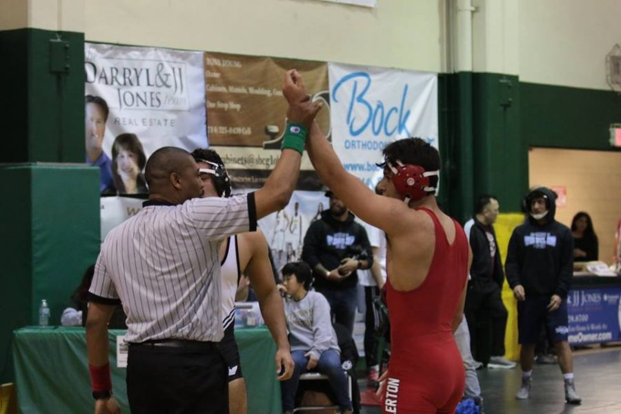 Senior Isaul Castaneda getting his hand raised after pinning his opponent