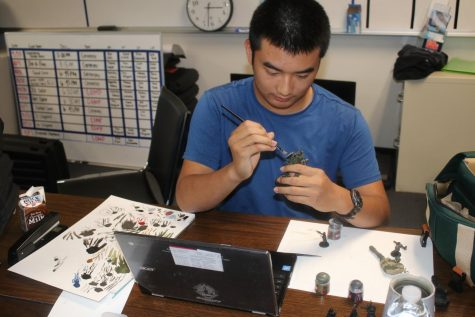 """Timothy Dinh was a member of the Warhammer Club. He paints his figurines, choosing the """"Astra Militarum"""" army, in which the quantity of your troops is more important than the quality. They have an advantage when they """"swarm"""" the enemy. Photo by Jose Perez."""