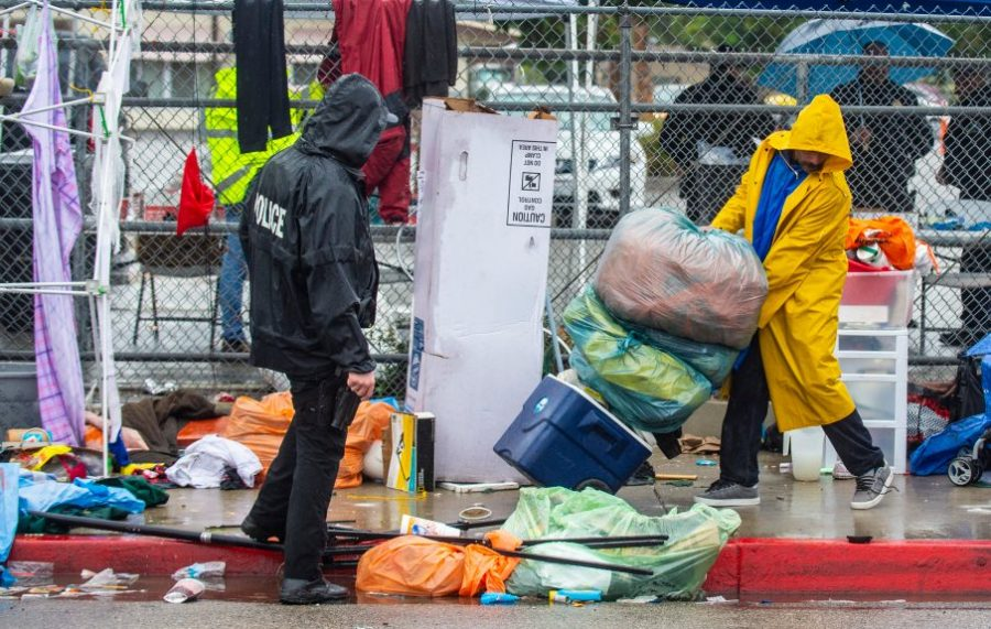 A police official supervises a homeless man as he removes his belongings from the sidewalk. Photo courtesy of Mark Rightmire, Orange County Register/SCNG.