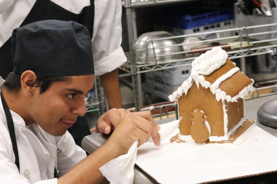 Senior+Ramses+Martinez+ices+his+Hawaiian-themed+gingerbread+house.+Photo+by+Jose+Perez.%0A