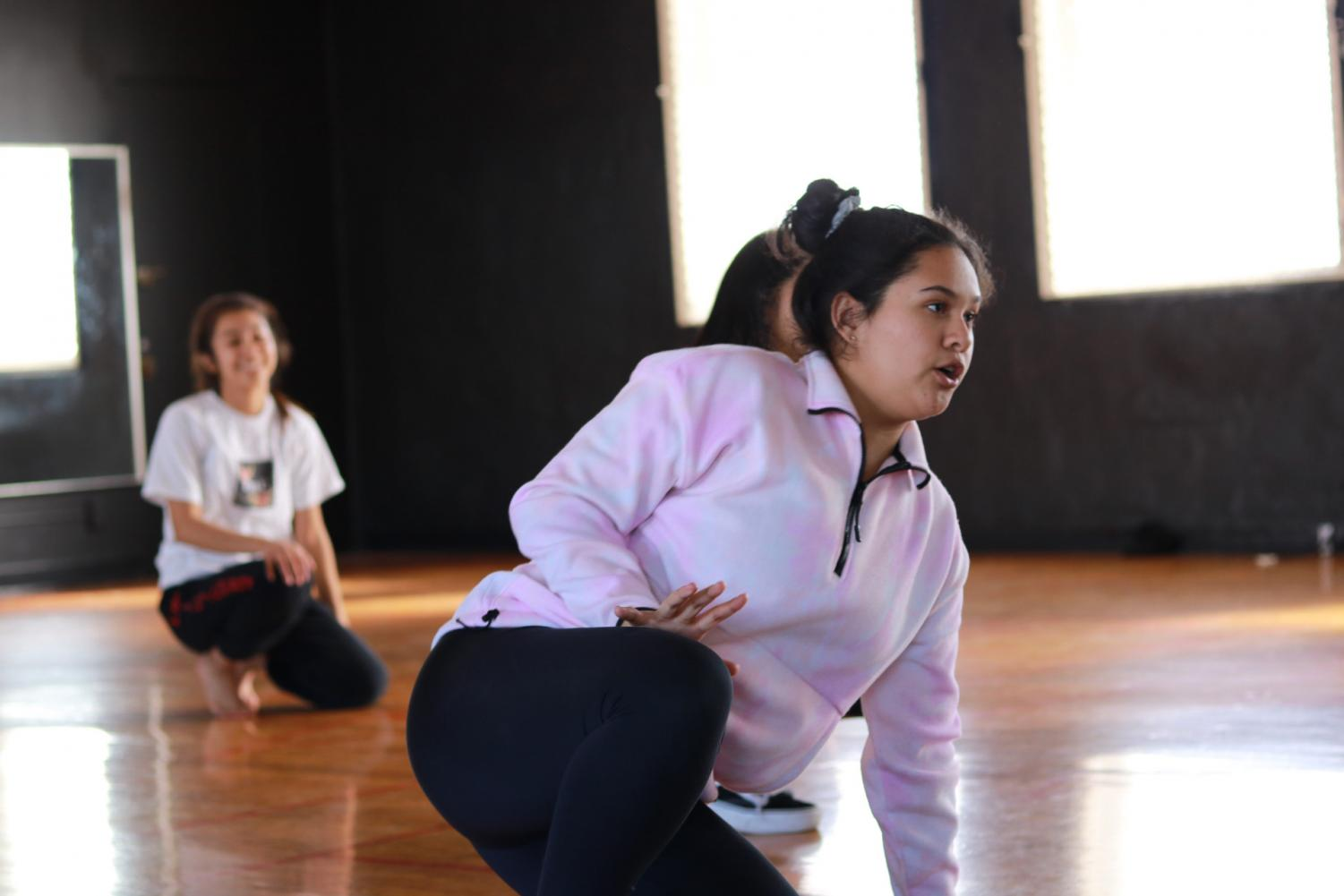 Dance Production isn't all about the pretty costumes; it's about the hard work. Student choreographer Karina Lopez reviews moves for Friday's performance. Photo by Jose Perez.