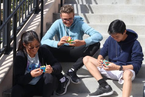 Sophomores Chelsea Yun, Landon Casaday and Kevin Le use slightly different methods to solve a Rubik's Cube. Photo by Lexi Ruesga.