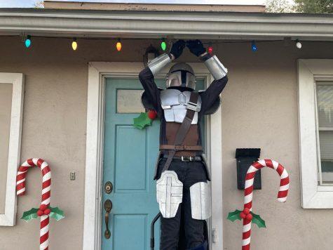 Senior Nathan Smith puts up Christmas lights wearing his foam Mandalorian armor. Photo courtesy of Lisa Smith.