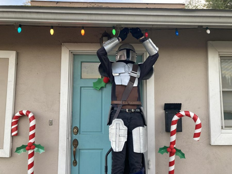 Senior+Nathan+Smith+puts+up+Christmas+lights+wearing+his+foam+Mandalorian+armor.+Photo+courtesy+of+Lisa+Smith.